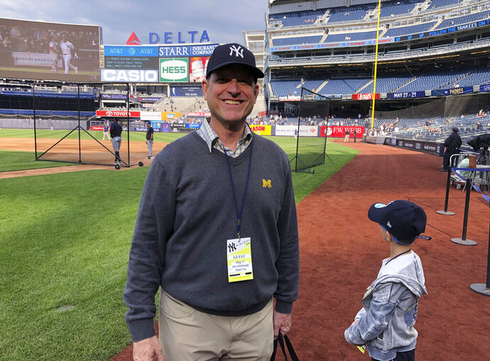 Michigan football coach Jim Harbaugh and his son, Jack, stand on the field at Yankee Stadium before the New York Yankees' baseball game against the Tampa Bay Rays on Friday, May 17, 2019, in New York. Shaking hands and posing for photos on the field during batting practice, Harbaugh wore a Yankees cap, a Michigan sweater vest and — of course — a crisp pair of khakis. He says he and his father had never been to Yankee Stadium before and it's a