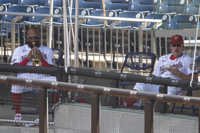 Washington Nationals' Emilio Bonifacio, left, plays his trumpet in the supplemental dugout as Andrew Stevenson yawns during the fourth inning of a baseball game against the New York Yankees at Nationals Park, Sunday, July 26, 2020, in Washington. (AP Photo/Alex Brandon)
