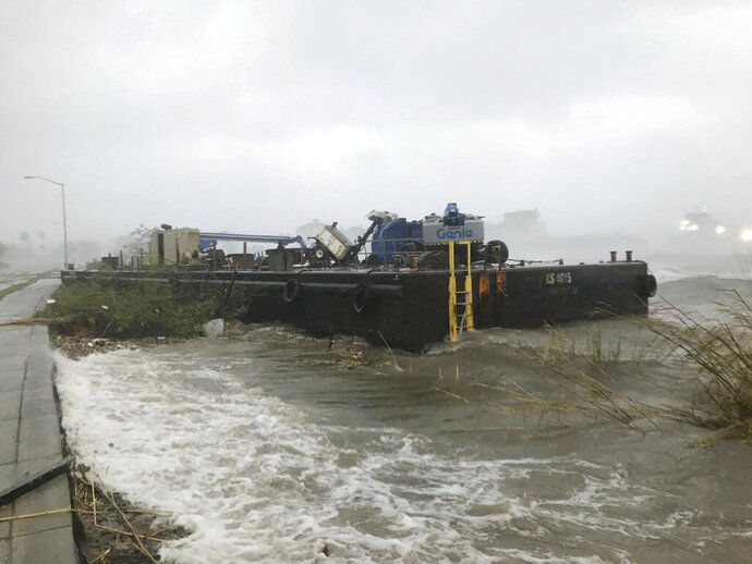 A barge runs aground along downtown Pensacola, Fla., on Wednesday, Sept. 16, 2020, as Hurricane Sally moves inland. Hurricane Sally lumbered ashore near the Florida-Alabama line Wednesday with 105 mph (165 kph) winds and rain measured in feet, swamping homes and trapping people in high water as it pushed inland for what could be a slow and disastrous drenching across the Deep South. (Tony Giberson//Pensacola News Journal via AP)