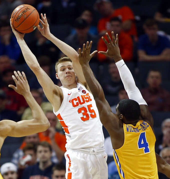 Syracuse's Buddy Boeheim (35) looks to pass the ball as Pittsburgh's Jared Wilson-Frame (4) defends during the first half of an NCAA college basketball game in the Atlantic Coast Conference tournament in Charlotte, N.C., Wednesday, March 13, 2019. (AP Photo/Nell Redmond)