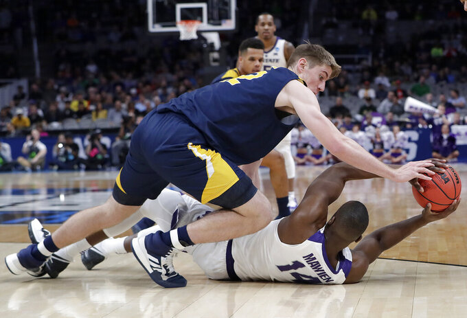 UC Irvine forward Tommy Rutherford, top, defends Kansas State forward Makol Mawien (14) during the first half of a first round men's college basketball game in the NCAA Tournament Friday, March 22, 2019, in San Jose, Calif. (AP Photo/Chris Carlson)