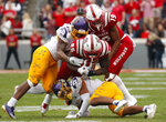 North Carolina State's Reggie Gallaspy II (25) gets some help from teammate C.J. Riley (19) as he fights for yardage against East Carolina's Nate Harvey (40) and Warren Saba (17) during the first half of NCAA college football game in Raleigh, N.C., Saturday, Dec. 1, 2018. (AP Photo/Chris Seward)