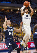 "File-This Feb. 9, 2019, file photo shows Marquette guard Markus Howard, right, going up for a basket against Villanova guard Joe Cremo, left, during the first half of an NCAA college basketball game in Milwaukee. Howard, a 5-11 junior, is fourth in the nation scoring at 25.2 points. ""My whole life, I've played above age,"" said Howard, who had 38 points in Saturday's win against reigning national champion Villanova. ""I always played three and four years older than what I was. I played against guys that were older than me, stronger than me, taller than me. ... So when I got to college, it was something that I really wasn't used to seeing."" (AP Photo/Darren Hauck, File)"