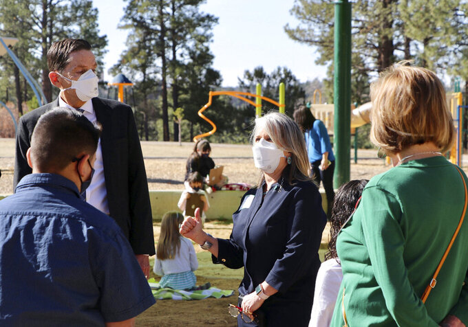 FILE - This April 5, 2021, file photo provided by the Office of the Governor shows New Mexico Gov. Michelle Lujan Grisham, center, with Aspen Elementary School Principal Michele Altherr, right, and left, Dr. Kurt Steinhaus, Los Alamos Public Schools Superintendent during a visit to Aspen Elementary School in Los Alamos, N.M. New Mexico Education Secretary Ryan Stewart is the latest cabinet secretary to call it quits during the pandemic. The education post will be filled by former Los Alamos Superintendent Kurt Steinhaus, 67, seen left, starting August 20, Gov. Michelle Lujan Grisham announced Thursday, July 29. (Nora Meyers Sackett/Office of the Governor via AP, File)