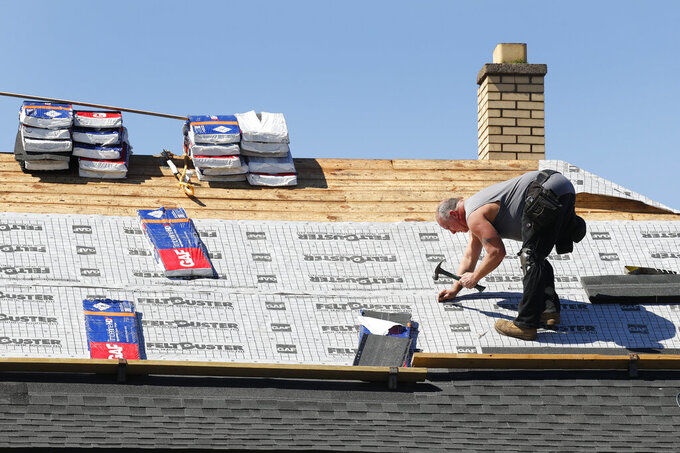 A roofer works on new shingles in Warren, Mich., Thursday, April 2, 2020. The coronavirus COVID-19 outbreak has triggered a stunning collapse in the U.S. workforce with 10 million people losing their jobs in the past two weeks and economists warn unemployment could reach levels not seen since the Depression, as the economic damage from the crisis piles up around the world. (AP Photo/Paul Sancya)