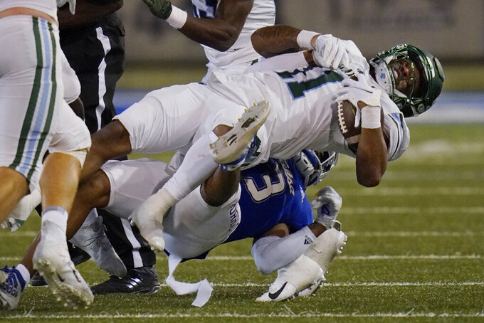 Tulane running back Amare Jones (11) is tackled by Tulsa safety Cristian Williams (3) during the second half of an NCAA college football game in Tulsa, Okla., Thursday, Nov. 19, 2020. (AP Photo/Sue Ogrocki)