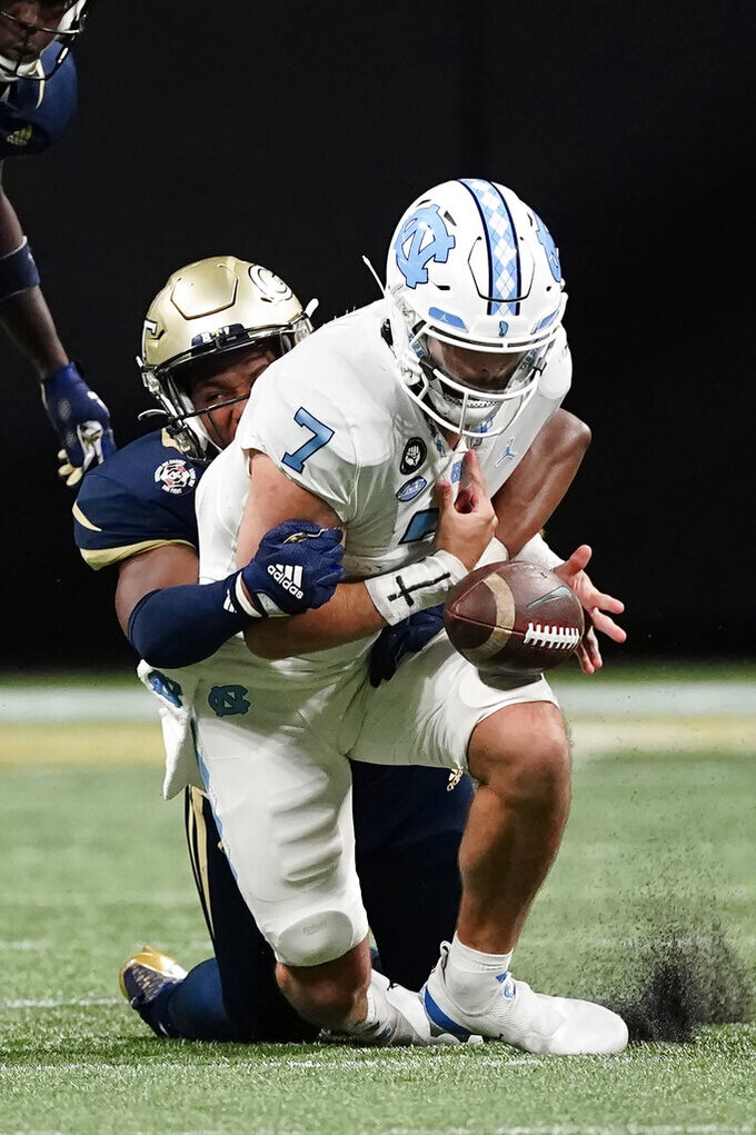 North Carolina quarterback Sam Howell (7) fumbles as he is tackled by Georgia Tech defensive lineman Jordan Domineck. during the first half of an NCAA college football game Saturday, Sept. 25, 2021, in Atlanta. Georgia Tech recovered the ball. (AP Photo/John Bazemore)