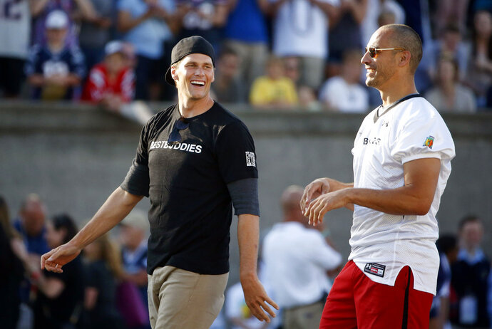 FILE - In this May 29, 2015 file photo, New England Patriots quarterback Tom Brady, left, walks with former Patriots tight end Christian Fauria during the Best Buddies Challenge charity football game in Boston. Boston sports radio station WEEI announced Wednesday, Feb. 14, 2018, that live programs will halt from 6 a.m. to 6 p.m. on Friday while employees receive