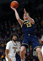 Michigan's Ignas Brazdeikis, right, lays up as Minnesota's Jordan Murphy looks on in the second half of an NCAA college basketball game Thursday, Feb. 21, 2019, in Minneapolis. (AP Photo/Jim Mone)