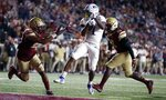 Kansas running back Pooka Williams Jr. (1) scores against Boston College defensive back Mehdi El Attrach (25) and linebacker John Lamot (28) during the second half of an NCAA college football game in Boston, Friday, Sept. 13, 2019. (AP Photo/Michael Dwyer)