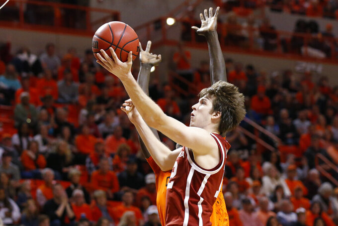Oklahoma guard Austin Reaves, front, shoots in front of Oklahoma State forward Yor Anei, rear, in the second half of an NCAA college basketball game in Stillwater, Okla., Saturday, Feb. 22, 2020. (AP Photo/Sue Ogrocki)