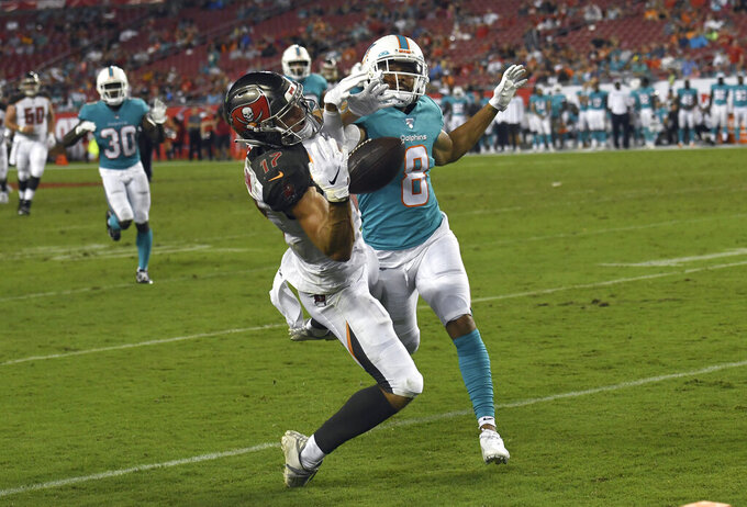 Miami Dolphins defensive back Tyler Patmon (8) hits with Tampa Bay Buccaneers wide receiver Justin Watson (17) on a pass play during the second half of an NFL preseason football game Friday, Aug. 16, 2019, in Tampa, Fla. Officials threw a penalty flag on the play and then picked it up. Buccaneers head coach Bruce Arians challenged the play and officials ruled there was pass interference. (AP Photo/Jason Behnken)
