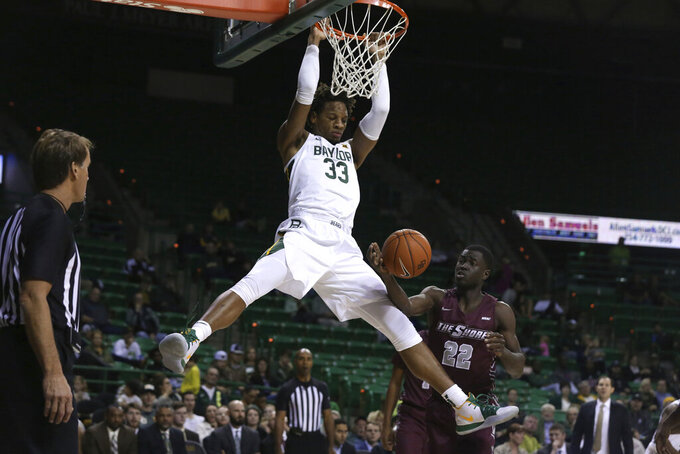 Baylor forward Freddie Gillespie scores over Maryland-Eastern Shore forward Gabriel Gyamfi, right, in the second half of an NCAA college basketball game, Tuesday, Dec. 3, 2019, in Waco, Texas. Baylor won 78-46. (AP Photo/Rod Aydelotte)