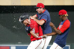 Minnesota Twins' Max Kepler, left, gets a water shower after his walk-off, bases-loaded single off Detroit Tigers pitcher Gregory Soto in the 10th inning of a baseball game, Monday, July 26, 2021, in Minneapolis. The Twins won 6-5. (AP Photo/Jim Mone)