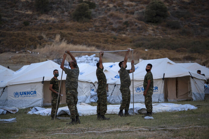 Greek soldiers set up UNHCR tents at a shooting range to accommodate refugees, in Lesbos Island, Greece, Friday, Sept. 11, 2020. Some thousands of refugees and migrants have spent a third night in the open on the Greek island of Lesbos after two consecutive nights of fires in the notoriously overcrowded Moria camp left them homeless. (AP Photo/Petros Giannakouris)
