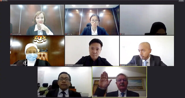In this image from video released by Malaysian Judiciary, Nathaniel Cary, a forensic pathologist, bottom right, raises his hand to take his oath ahead of his testimony being provided online from the United Kingdom during a Malaysian virtual inquest on Monday, Nov. 30, 2020. The British pathologist said there was no positive evidence of sexual assault on French-Irish teenager Nora Anne Quorin, who was found dead last year after vanishing from a Malaysian jungle resort, but that he couldn't fully rule it out due to severe body decomposition. (Malaysian Judiciary via AP)