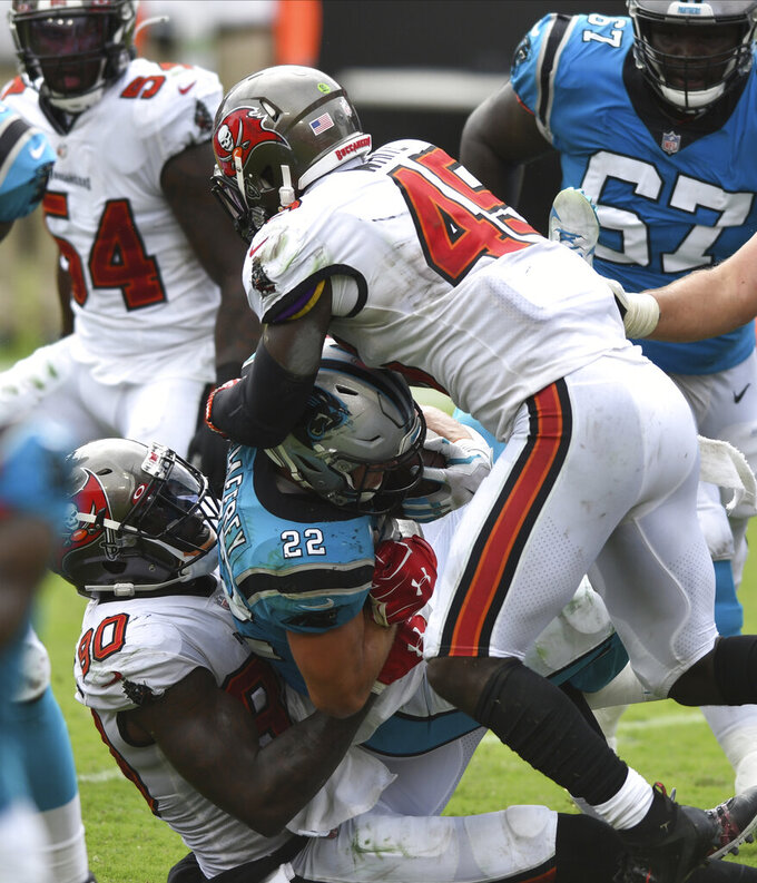 Tampa Bay Buccaneers defensive end Jason Pierre-Paul (90) and linebacker Devin White (45) take down Carolina Panthers running back Christian McCaffrey (22) during the second half of an NFL football game Sunday, Sept. 20, 2020, in Tampa, Fla. (AP Photo/Jason Behnken)
