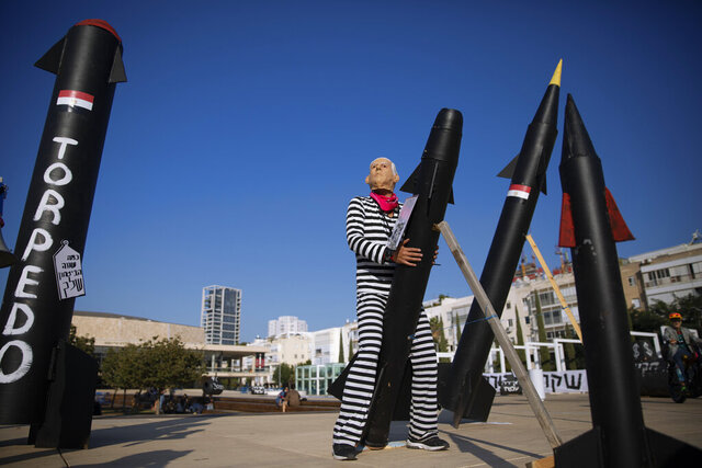 A protester wearing a rubber mask representing Israeli Prime Minister Benjamin Netanyahu holds a mock rocket during a protest in Tel Aviv, Israel, Wednesday, Nov. 11, 2020. Critics accuse Netanyahu of allowing the United Arab Emirates to acquire advanced weapons from the U.S. as part of a recent deal establishing diplomatic ties, an accusation that Netanyahu denies. (AP Photo/Oded Balilty)