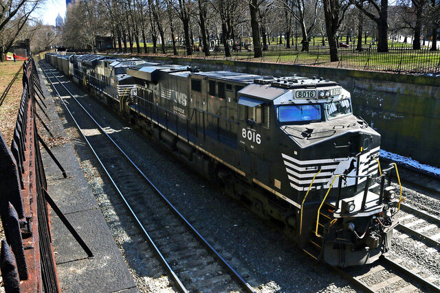 FILE- In this March 26, 2018, file photo, a Norfolk Southern freight train rolls through downtown Pittsburgh. Norfolk Southern's fourth-quarter profit improved slightly even though it hauled 1% less freight because the railroad controlled expenses tightly as the economy continued to slowly recover from last year's widespread shutdowns during the coronavirus pandemic.  (AP Photo/Gene J. Puskar, File)