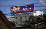 An election campaign billboard shows Venezuela's late President Hugo Chavez, left, with President Nicolas Maduro and the Spanish phrase