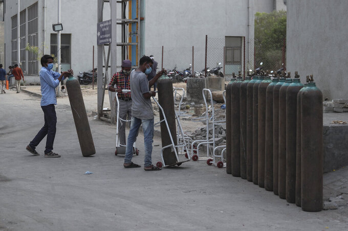 Workers stack empty oxygen cylinders near an oxygen plant at a government COVID-19 hospital in Ahmedabad, India, Tuesday, April 27, 2021. The COVID-19 death toll in India has topped 200,000 as the country endures its darkest chapter of the pandemic yet. (AP Photo/Ajit Solanki)