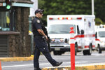A security guard stands outside the main gate at Joint Base Pearl Harbor-Hickam, in Hawaii, Wednesday, Dec. 4, 2019. A shooting at Pearl Harbor Naval Shipyard in Hawaii left at least one person injured Wednesday, military and hospital officials said. Joint Base Pearl Harbor-Hickam spokesman Charles Anthony confirmed that there was an active shooting at Pearl Harbor Naval Shipyard. (AP Photo/Caleb Jones)