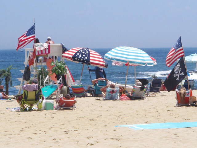 Flags line the beach in Belmar, N.J., on June 28, 2020. With large crowds expected at the Jersey Shore for the July Fourth weekend, some are worried that a failure to heed mask-wearing and social distancing protocols could accelerate the spread of the coronavirus. (AP Photo/Wayne Parry)