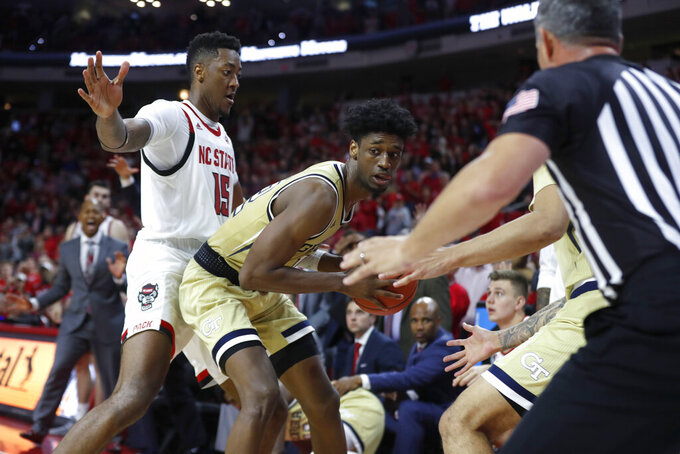 Georgia Tech's Khalid Moore (12) pulls in a loose ball after North Carolina State's Devon Daniels tried to throw the ball to Manny Bates (15) with less than 10 seconds left in an NCAA college basketball game Tuesday, Nov. 5, 2019, in Raleigh, N.C. (Ethan Hyman/The News & Observer via AP)