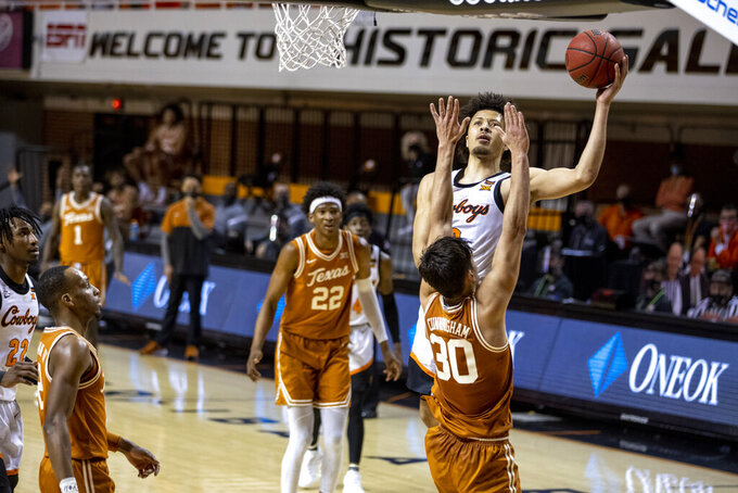 Oklahoma State guard Cade Cunningham (2) shoots a layup over Texas forward Brock Cunningham (30) during the first overtime of the NCAA college basketball game in Stillwater, Okla., Saturday, Feb. 6, 2021. (AP Photo/Mitch Alcala)