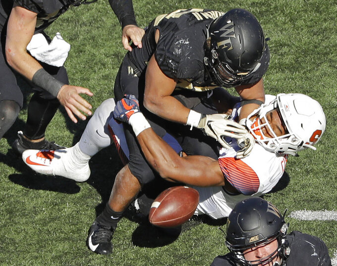 Wake Forest's Matt Colburn, top, fumbles the ball as he is tackled by a Syracuse player in the second half of an NCAA college football game in Charlotte, N.C., Saturday, Nov. 3, 2018. Syracuse recovered the ball. (AP Photo/Chuck Burton)