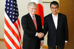 Japanese Foreign Minister Taro Kono, right, and U.S. National Security Advisor John Bolton, left, shake hands prior to their meeting in Tokyo Monday, July 22, 2019. (AP Photo/Eugene Hoshiko)