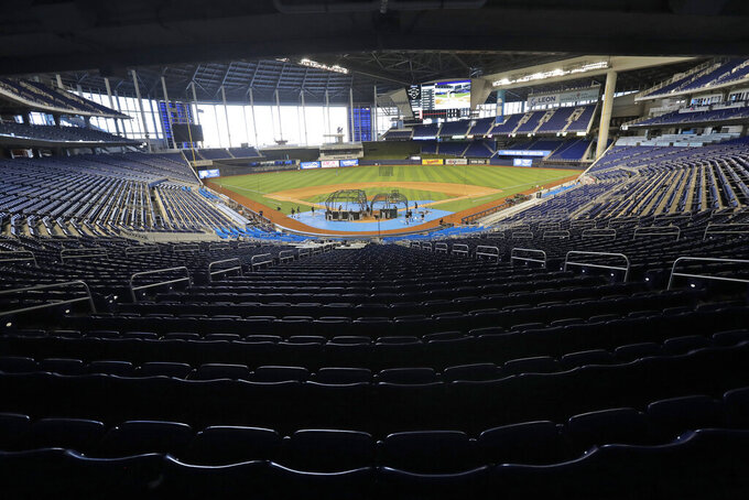 FILE - In this Thursday, July 16, 2020, file photo, the Miami Marlins take batting practice during a baseball workout at Marlins Park in Miami. The Marlins, one of the most under-the-radar teams in sports, have making news lately, all of it bad. Overtaken by a coronavirus outbreak, the team must scramble for roster replacements as they try salvage a season barely underway.(AP Photo/Wilfredo Lee, File)