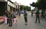 A soldier walks with his family near the military base where a car bomb exploded in Cucuta, Colombia, Tuesday, June 15, 2021. Colombian authorities still have not confirmed how many were injured in the explosion. (AP Photo/Ferley Ospina)