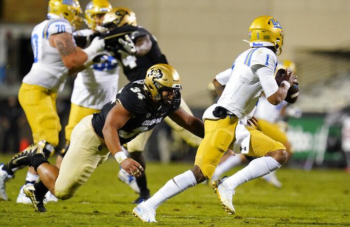 UCLA quarterback Dorian Thompson-Robinson, right, evades Colorado defensive end Mustafa Johnson in the second half of an NCAA college football game Saturday, Nov. 7, 2020, in Boulder, Colo. (AP Photo/David Zalubowski)