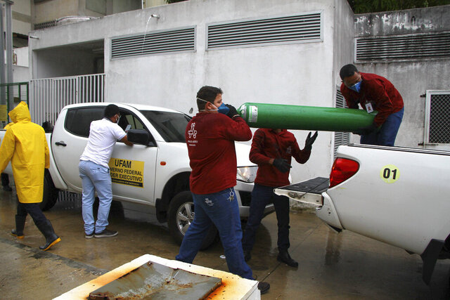 Amazonas Federal University's workers carry empty oxygen tanks at the Getulio Vargas Hospital amid the new coronavirus pandemic, Manaus, Brazil, Thursday, Jan. 14, 2021. Scores of COVID-19 patients in the Amazon rainforest's biggest city will be transferred out of state as the local health system collapses and dwindling stocks of oxygen tanks begin to falter. (AP Photos/Edmar Barros)