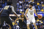 West Virginia guard Jermaine Haley (10) is defended by Oklahoma State forward Kalib Boone (22) and guard Avery Anderson III (0) during the second half of an NCAA college basketball game Tuesday, Feb. 18, 2020, in Morgantown, W.Va. (AP Photo/Kathleen Batten)