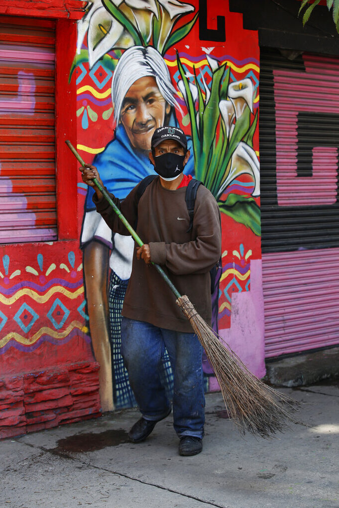 Wearing a mask to curb the spread of the new coronavirus, a street sweeper works in the Iztapalapa Borough of Mexico City, Monday, Aug. 9, 2021. Mexico will ask the United States to send at least 3.5 million more doses of COVID-19 vaccine as the country faces a third wave of infections, President Andres Manuel Lopez Obrador said Monday. (AP Photo/Marco Ugarte)
