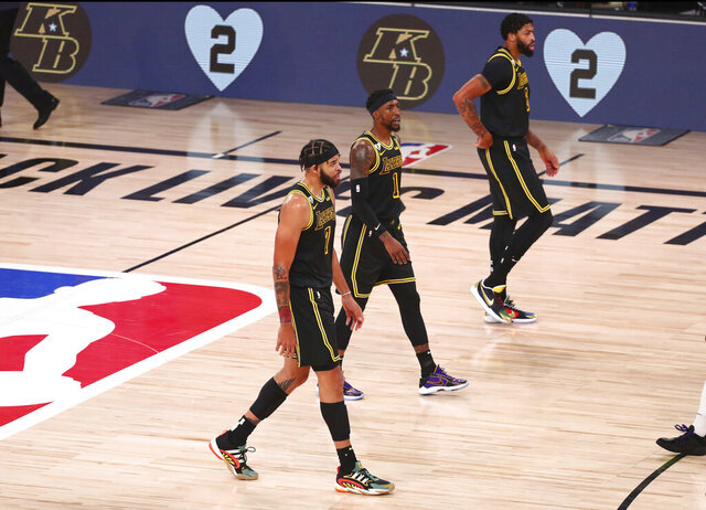"FILE - In this Aug. 24, 2020, file photo, Los Angeles Lakers center JaVale McGee (7), guard Kentavious Caldwell-Pope (1) and forward Anthony Davis (3) walk in front of the boards remembering late Los Angeles Lakers player Kobe Bryant in the first half of Game 4 of an NBA basketball first-round playoff series against the Portland Trail Blazers in Lake Buena Vista, Fla. The jerseys will be hanging in their lockers when the Los Angeles Lakers arrive for Game 2 of the NBA Finals on Friday night, Oct. 2. Black jerseys, trimmed in gold, a snakeskin print on the exterior to make it further unique.T hey are the Black Mamba jerseys. Designed by Kobe Bryant — and now worn for Kobe Bryant. ""We never want to lose in these jerseys,"" Lakers forward Anthony Davis said.(Kim Klement/Pool Photo via AP, File)"