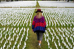 Artist Suzanne Brennan Firstenberg walks among thousands of white flags planted in remembrance of Americans who have died of COVID-19, Tuesday, Oct. 27, 2020, near Robert F. Kennedy Memorial Stadium in Washington. Firstenberg's temporary art installation, called