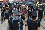Masked protesters march in Hong Kong on Saturday, Oct. 5, 2019. All subway and trains services are closed in Hong Kong after another night of rampaging violence that a new ban on face masks failed to quell. (AP Photo/Vincent Thian)