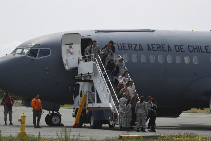 Relatives of passengers of a missing military plane arrive in a Chilean military airplane to an airbase in Punta Arenas, Chile, Wednesday, Dec. 11, 2019. Searchers using planes, ships and satellites were combing the Drake Passage on Tuesday, hunting for the plane carrying 38 people that vanished en route to an Antartica base. (AP Photo/Fernando Llano)
