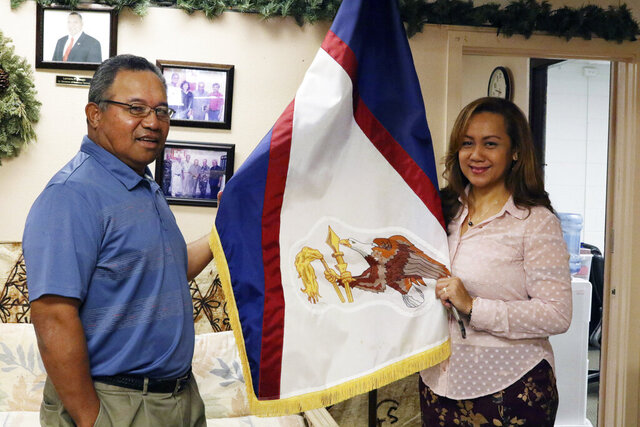 In this Jan. 10, 2020 photo, Filipo Ilaoa, left, and Bonnelley Pa'uulu pose with the flag of American Samoa at the American Samoa government office in Honolulu. Some American Samoans worry a federal judge's recent ruling in Utah saying those born in the U.S. territory should be recognized as U.S. citizens could threaten