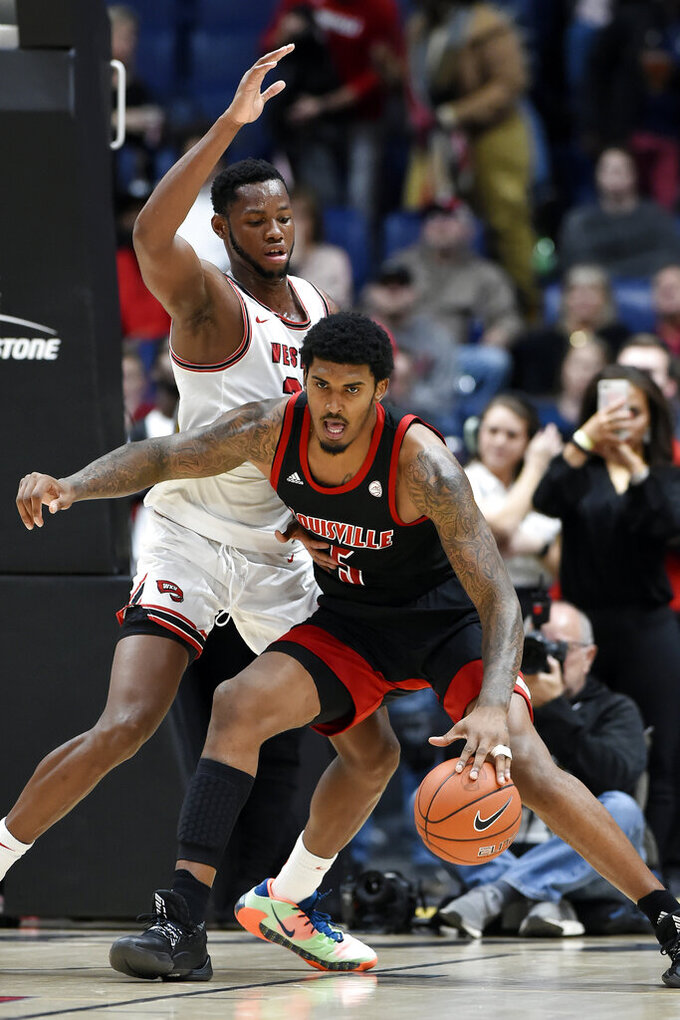 Louisville forward Malik Williams (5) is defended by Western Kentucky center Charles Bassey (23) during the first half of an NCAA college basketball game Friday, Nov. 29, 2019, in Nashville, Tenn. (AP Photo/Mark Zaleski)