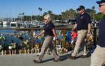 National Transportation Safety Board member Jennifer Homendy and her team walk past a memorial for the victims of a dive boat fire at Santa Barbara Harbor on Wednesday, Sept. 4, 2019 in Santa Barbara, Calif. A fire raged through a boat carrying recreational scuba divers anchored near an island off the Southern California Coast on Monday, Sept. 2, leaving multiple people dead.(AP Photo/Christian Monterrosa )