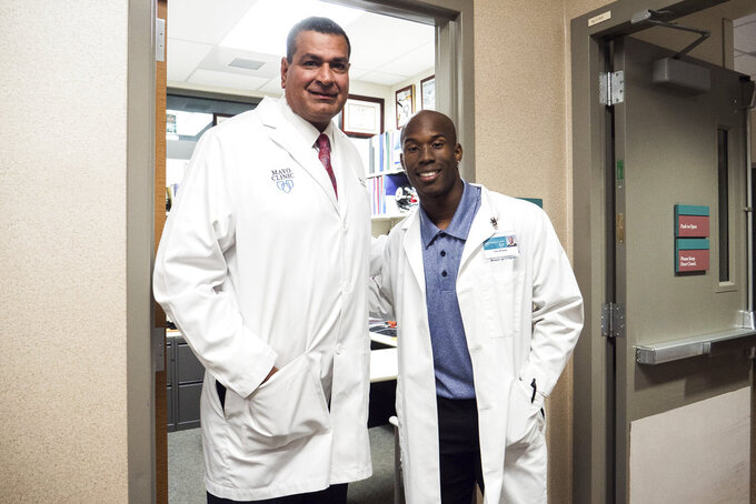 In this June 28, 2018 photo provided by Arizona State University Media Relations, Arizona State wide receiver Kyle Williams, right, poses with Dr. Anikar Chhabra, the team physician and director of sports medicine, at the Mayo Clinic in Scottsdale, Ariz. Summers are hardly a break for most college athletes, especially football players. Almost all take classes to lighten their loads in season. Still, many college football players work summer jobs and internships or do volunteer work. At Arizona State, receiver Kyle Williams is preparing to be a surgeon. (Arizona State University Media Relations via AP)