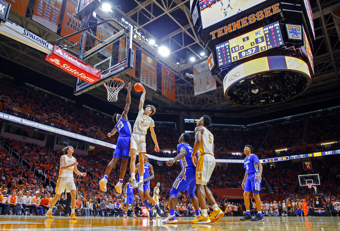 Tennessee forward Drew Pember (3) dunks the ball over Memphis center Malcolm Dandridge (23) during the first half of an NCAA college basketball game Saturday, Dec. 14, 2019, in Knoxville, Tenn. (AP Photo/Wade Payne)