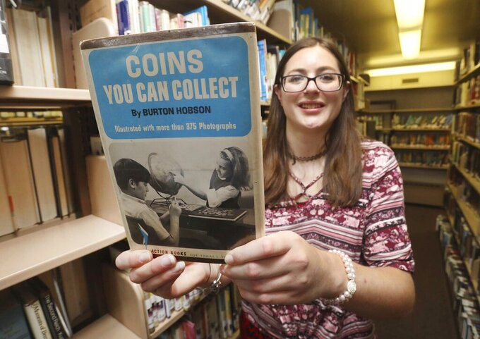 """Plymouth Pa. Public Library Director Laura Keller holds up the book """"Coins You Can Collect"""", Tuesday Aug. 3 2021, after it was returned 50-years overdue.  Included with the book was a letter and $20 donation. (Dave Scherbenco/The Citizens' Voice via AP)"""