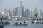 In this Thursday, July 4, 2019 photo, with the skyline of Panama City in the background, fishermen ride their boat on Panama City bay. The capital of Panama, is a modern city framed by the Pacific Ocean and the man-made Panama Canal. (AP Photo/Arnulfo Franco)