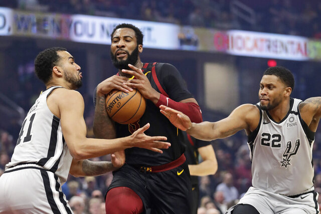 Cleveland Cavaliers' Andre Drummond, center, drives between San Antonio Spurs' Trey Lyles, left, and Rudy Gay, right, in the first half of an NBA basketball game, Sunday, March 8, 2020, in Cleveland. (AP Photo/Tony Dejak)