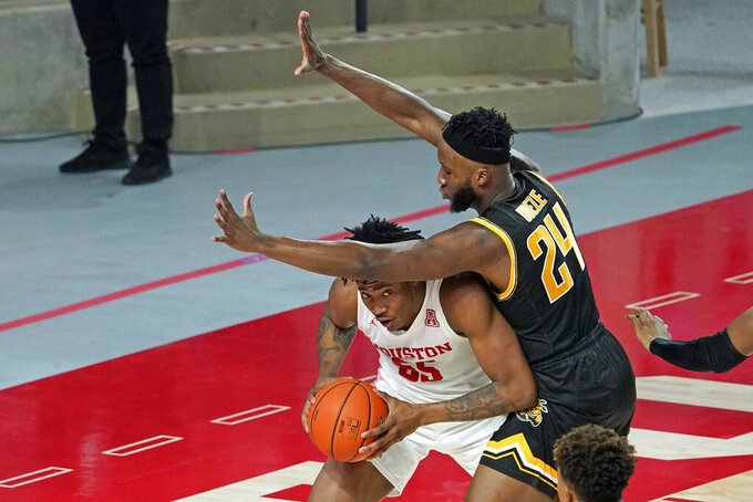 Houston's Brison Gresham, left, looks to pass the ball as Wichita State's Morris Udeze (24) defends during the second half of an NCAA college basketball game Wednesday, Jan. 6, 2021, in Houston. (AP Photo/David J. Phillip)